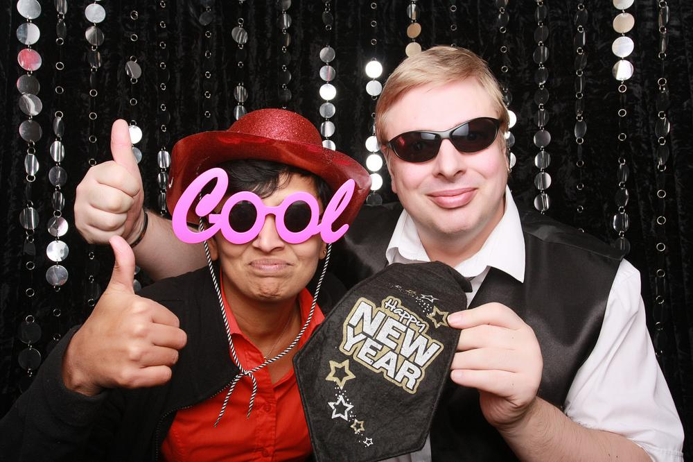 a happy couple sitting in a black tie photobooth